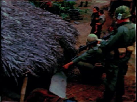 december 19, 1967 soldiers searching a village and questioning civilians / bong son, south vietnam - 南ベトナム点の映像素材/bロール