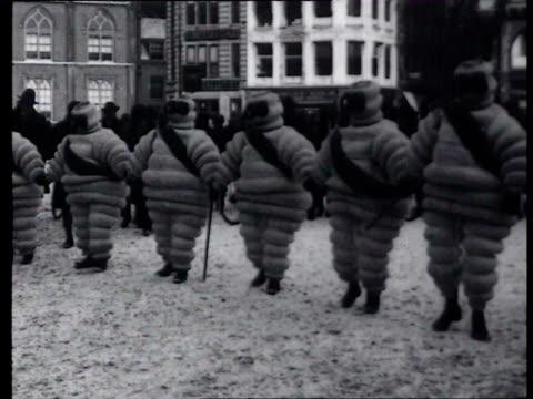 stockvideo's en b-roll-footage met december 1929 b/w six michelin men walk hand in hand over the dam in amsterdam, funny / amsterdam, noord-holland, netherlands - noord holland