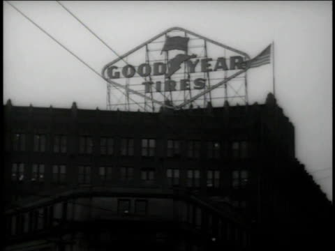 December 1942 WS Goodyear Tires sign on top of building beside American flag / Akron, Ohio, United States