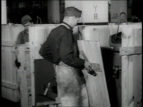december 1942 ws men crating gun mounts and hammering the boxes closed / pontiac, michigan, united states  - general motors stock videos & royalty-free footage
