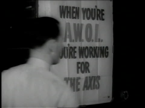 December, 1942 CU people walking by a sign saying When You're AWOL You're working for the Axis / Akron, Ohio, United States