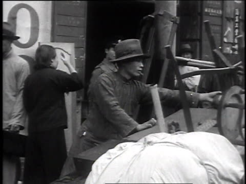 December 2 1935 MONTAGE People in streets of Shanghai packing furniture and trunks onto truck and rickshaws as soldiers with rifles parade past /...