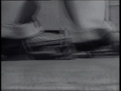 vídeos y material grabado en eventos de stock de december 23, 1936 man wearing a contraption with bellows on his feet to blow air on his face as he walks down the street - invento