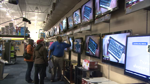 december 24, 2010 customers watching wall of in-store televisions at best buy while speaking with a store clerk / united states - elektrogeschäft stock-videos und b-roll-filmmaterial