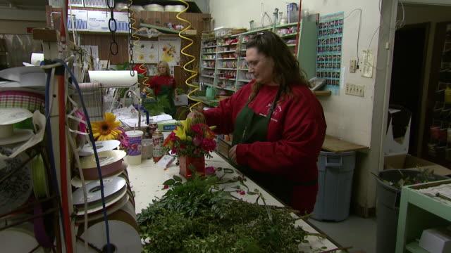 december 3, 2008 florist finalizing a small arrangement at tillie's flower shop / wichita, kansas, united states - flower arrangement stock videos & royalty-free footage
