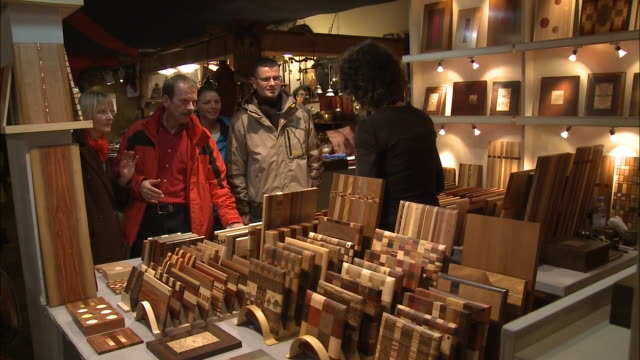 vídeos de stock, filmes e b-roll de december 3, 2009 shoppers selecting purchases at woodworking stall with vendor's assistance / berlin, germany - grupo pequeno de pessoas