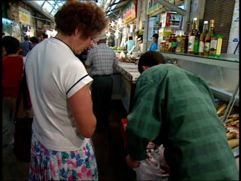 vidéos et rushes de december 31, 1966 worker helps a shopper at the market / israel - temps réel