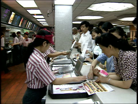 vídeos de stock, filmes e b-roll de december 7 1993 montage cashiers taking orders from customers in mcdonald's and customer browsing a menu / beijing china - enfoque de objeto sobre a mesa