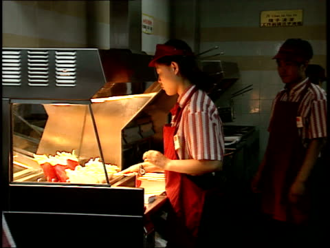 december 7 1993 montage worker preparing french fries at mcdonald's / beijing china - mcdonald's stock videos & royalty-free footage