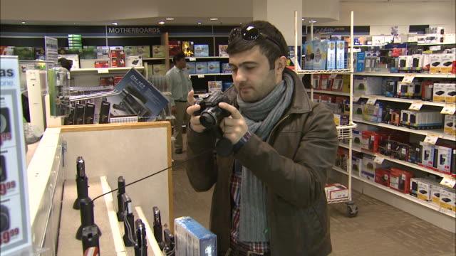 december 8 2010 zo customer examining digital camera beside display at micro center / united states - digital camera stock videos & royalty-free footage