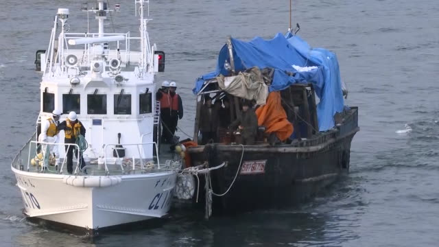 japan coast guard ship towing the north korean boat to hakodate port gv police arresting crew members of the north korean boat gv police and japan... - rimorchiare video stock e b–roll