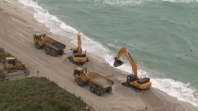 vídeos y material grabado en eventos de stock de decenas de camiones estan vertiendo miles de toneladas de arena blanca con particulas de no mas de 4 7 milimetros de diametro en miami beach - ee.uu