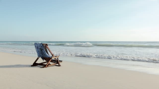 deck chair on sandy beach at water's edge - deckchair stock videos & royalty-free footage