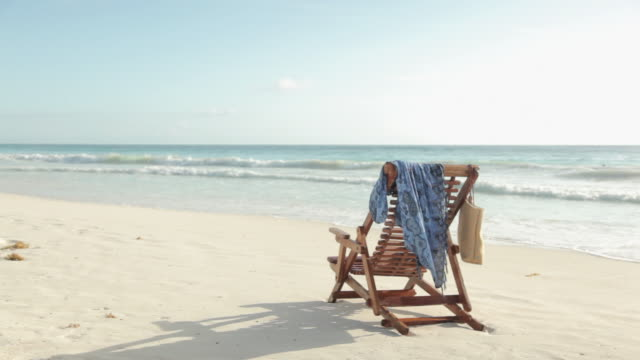deck chair on sandy beach at water's edge - deck chair stock videos & royalty-free footage