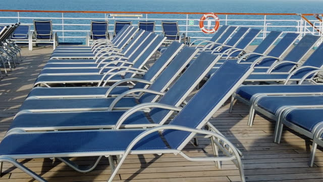 deck chairs arranged neatly in rows with a beautiful sunny blue sky with puffy clouds to enjoy - cruise vacation stock videos & royalty-free footage