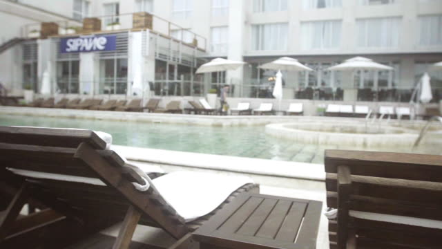 deck chairs lining poolside at luxury hotel - adirondack chair stock videos & royalty-free footage