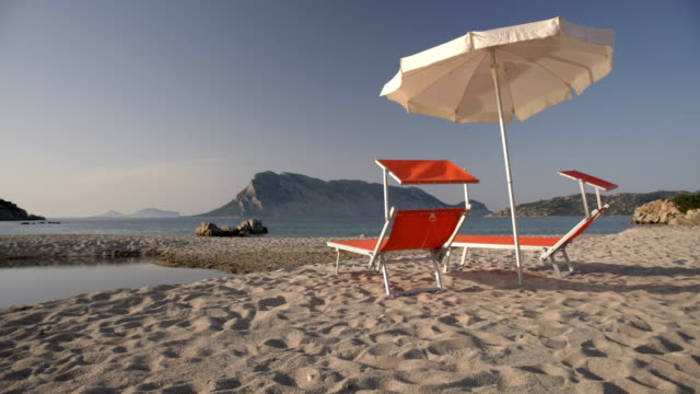 deck chairs on the beach at sunset - sardinien stock-videos und b-roll-filmmaterial