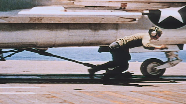 Deck crew removing chocks and preparing jets for takeoff from aircraft carrier Vought F8 Crusader taking off and flying overhead and pilot putting on...