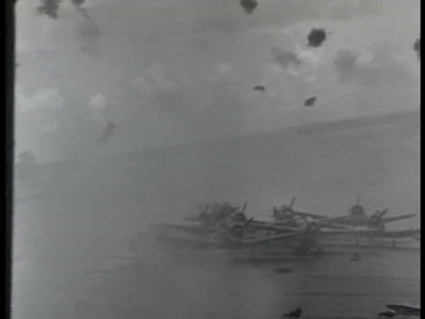 deck us battleship w/ anti-aircraft guns firing. airplanes on carrier deck. sky w/ anti-aircraft firing, bullet trail in sky, black smoke puffs. bomb... - anti aircraft stock videos & royalty-free footage