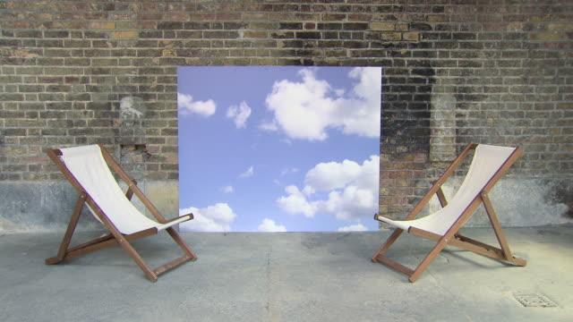 vídeos de stock e filmes b-roll de deckchairs and sky backdrop, teenage couple enter and sit on deckchairs - sentar se