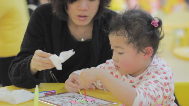 declining mum's help,asian girl insist on coloring picture herself - assertiveness stock videos & royalty-free footage