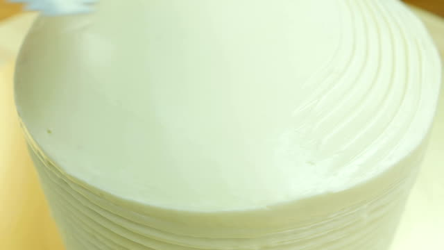 Decorate cake with butter cream. Front view. Close up. Slow motion.