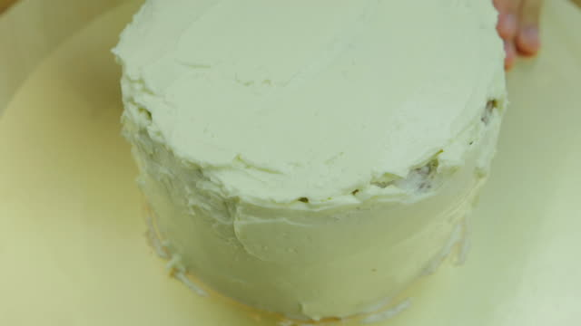 Decorate cake with butter cream. Front view. Close up. Time lapse.