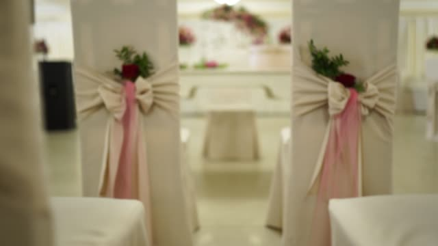 Decorated chairs at restaurant for wedding ceremony