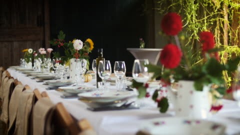 decorated dinner table with flowers for a large group of people inside a barn in summer. for a wedding or garden party. - barn stock videos & royalty-free footage