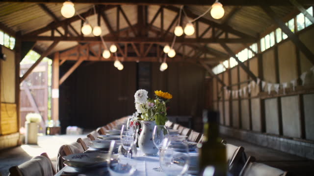 decorated dinner table with flowers for a large group of people inside a barn in summer. for a wedding or garden party. - wedding stock videos & royalty-free footage
