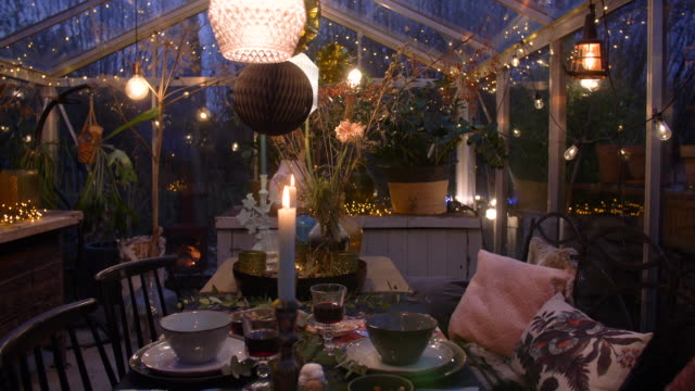 a decorated greenhouse in trendy christmas setting with dinner table, candles and christmas lights., 4k. - 観葉植物点の映像素材/bロール