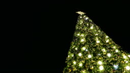 decorated & illuminated christmas tree for merry xmas party at night. Bright shiny golden bokeh light. Happy new year holiday celebration in december.