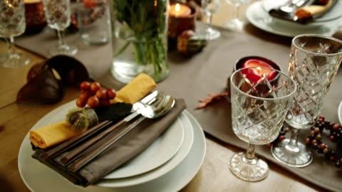 vídeos y material grabado en eventos de stock de mesa decorada para cena de acción de gracias con velas, calabazas, hojas y frutos secos - estación entorno y ambiente