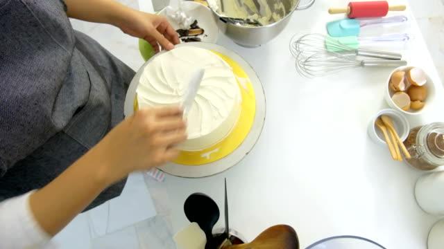 vidéos et rushes de décorer un gâteau à l'aide de la spatule angle offset - baking