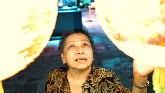 decorating chinese lantern : smiling elderly woman - electric lamp video stock e b–roll