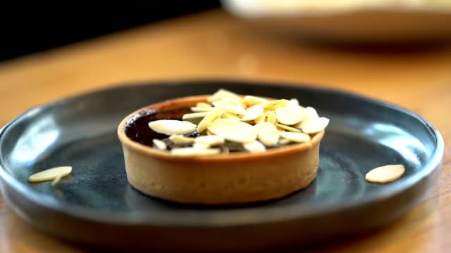 slomo decorating dark chocolate pie with sliced almond - decoration stock videos & royalty-free footage
