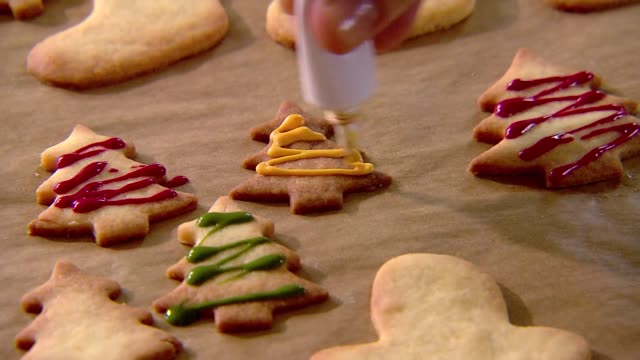 decorating gingerbread biscuits with frosting - クッキー点の映像素材/bロール