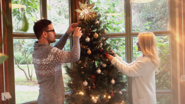 decorating the christmas tree - decorating the christmas tree stock videos & royalty-free footage