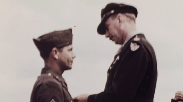 Decoration ceremony on flightline by parked B17s with commanding officer pinning medals on soldier sergeant and officer / Polebrook England United...