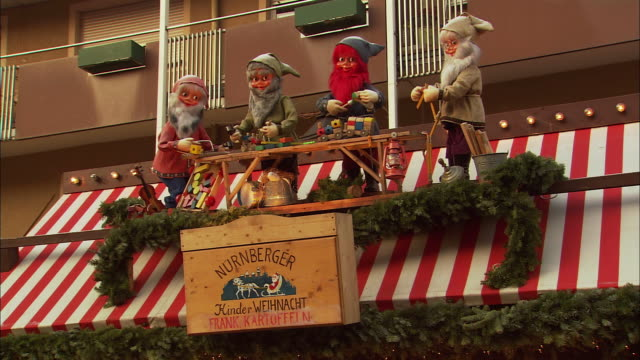 ws decoration with figurines of elves on rooftop of christmas market (kinderweihnacht) stall / nuremberg, bavaria, germany - エルフ点の映像素材/bロール