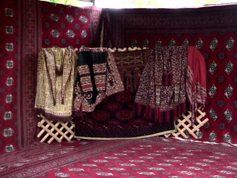 decoration with turkmen traditional cloths and carpets with turkmen musicians getting ready for performance during bakhshi musical contest,... - solo uomini di età media video stock e b–roll