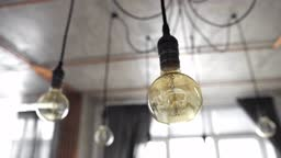 Decorative antique edison light bulbs with straight wire. Big vintage incandescent light bulbs hanging in modern kitchen. Inefficient filament light bulbs waste electricity. Dimmable, warm white,
