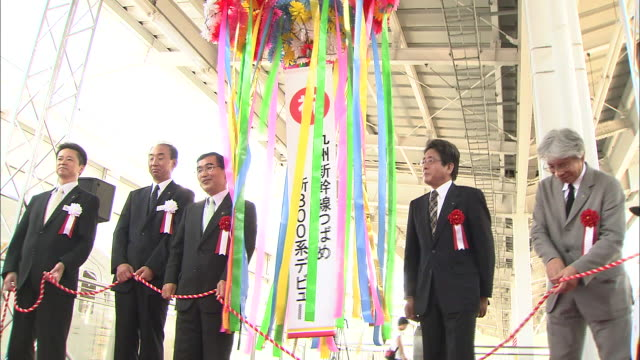 a decorative ball and streamers split during the departing ceremony of the kyushu shinkansen 800 series train as officials applaud - kyushu shinkansen stock videos & royalty-free footage
