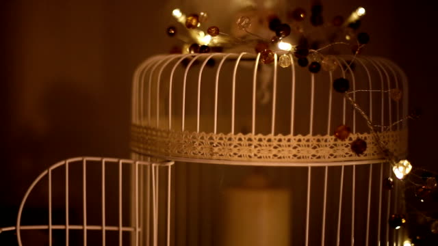 decorative cage with a candle on a wooden background.Monochrome