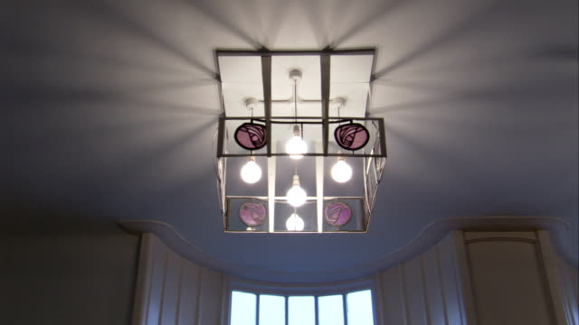 a decorative ceiling light illuminates a room in the glasgow school of art. available in hd. - decorative art stock videos and b-roll footage