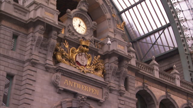 A decorative clock marks the time on a train station wall.