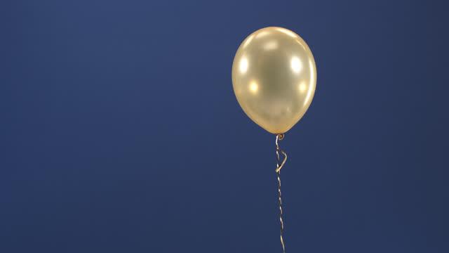 vídeos y material grabado en eventos de stock de un elemento decorativo - un globo de oro - aparece en el video como una sorpresa en una llave de croma, un regalo para el día de san valentín, cumpleaños, navidad o año nuevo. - globo de helio