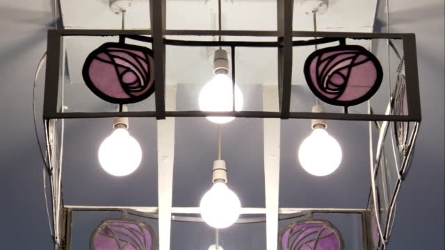 a decorative light fixture hangs from a ceiling in the glasgow school of art building. available in hd. - decorative art stock videos and b-roll footage