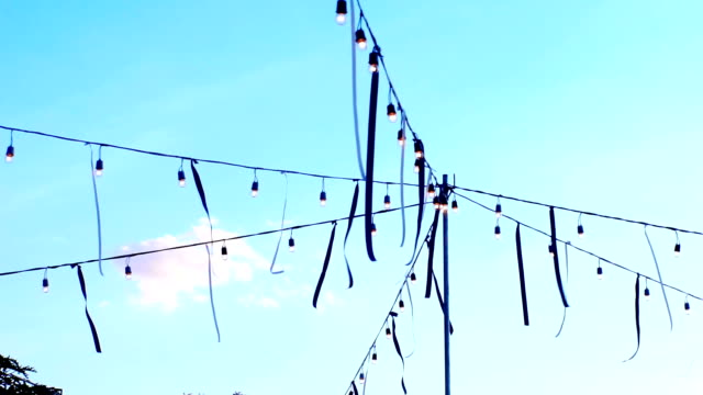 Decorative outdoors lights and ribbons on string wire for a party on soft blue background in the evening.
