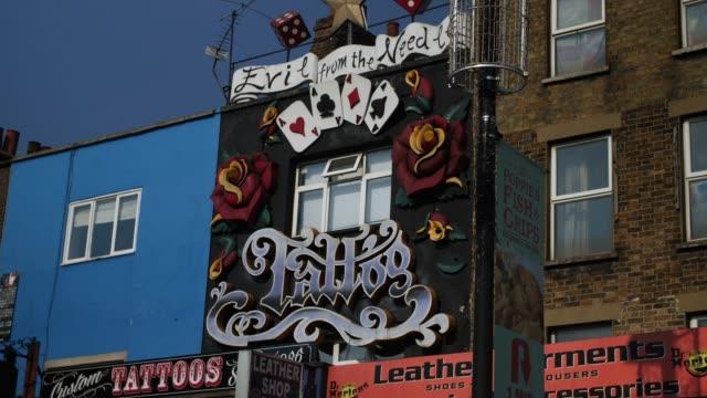 vídeos de stock e filmes b-roll de decorative shop front of tattoo parlour, camden - tatuagem